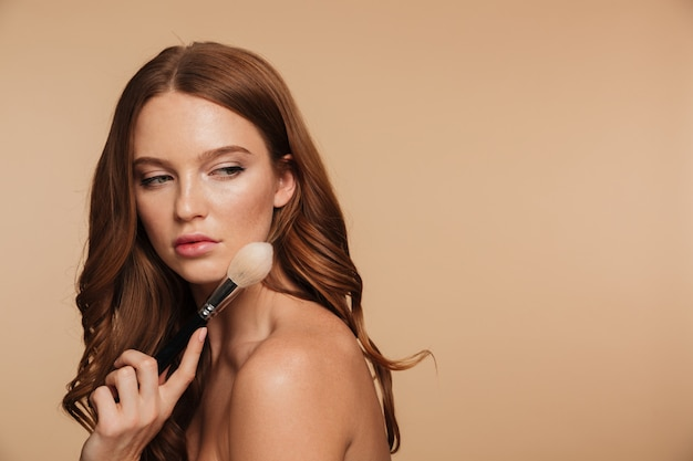 Beauty portrait of calm ginger woman with long hair posing sideways while looking back and holding cosmetics brush
