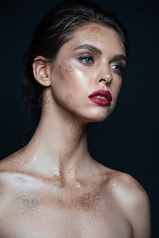 Beauty portrait of charming young woman with sparkling fashion makeup over black surface