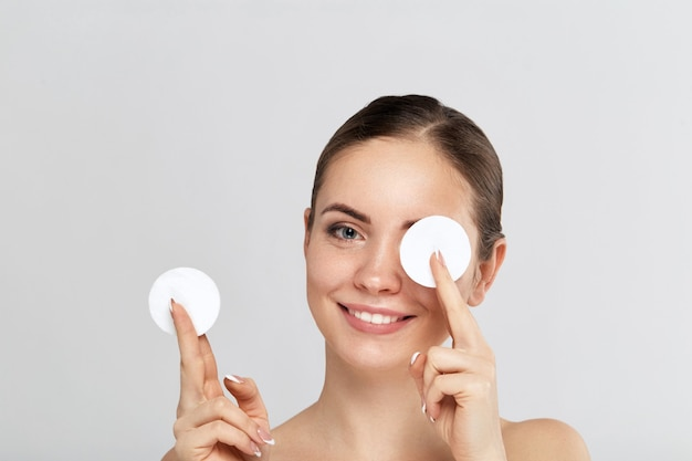 Beauty portrait of a cheerful young topless woman removing face make-up with a cotton pad