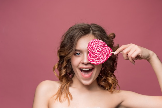 Beauty portrait of a cute girl in act to eat a candy over pink wall
