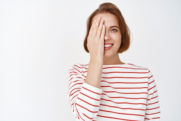 Beauty. portrait of cute smiling woman cover half face with hand and looking happy, showing before after cosmetics skin care effect, standing against white wall