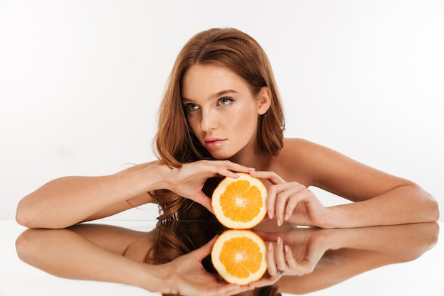 Beauty portrait of focused ginger woman with long hair reclines on mirror table while holding orange and looking away