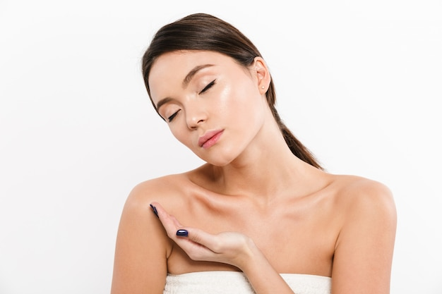Beauty portrait of gentle asian woman with closed eyes holding advertising product on her palm, isolated over white