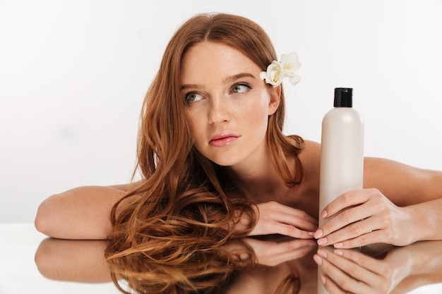 Beauty portrait of ginger woman with flower in hair sitting by the mirror table with bottle of lotion while looking away