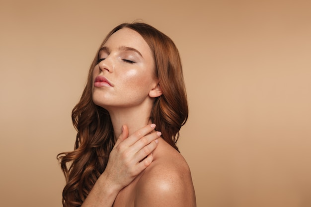 Beauty portrait of ginger woman with long hair posing sideways with closed eyes