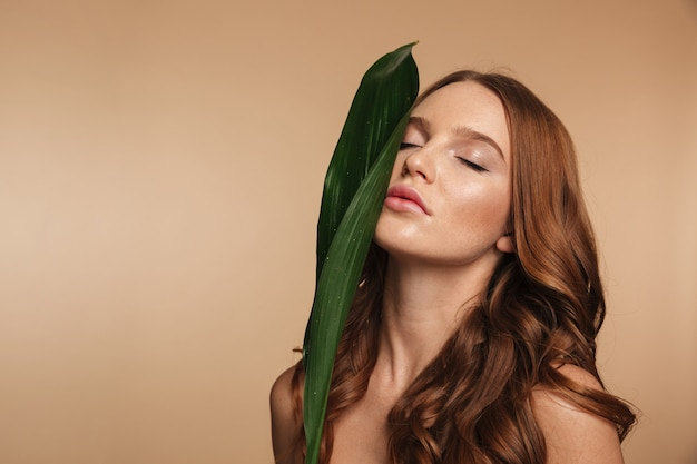 Beauty portrait of ginger woman with long hair posing with green leaf