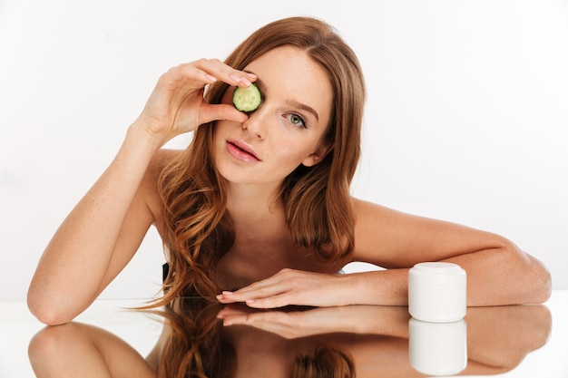 Beauty portrait of ginger woman with long hair sitting by the mirror table with fresh cucumber and body cream while looking