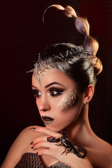 Beauty portrait of a girl with a live scorpion. studio photography of a fashion portrait.