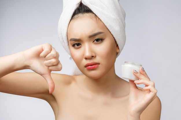 Beauty portrait of half-naked asian woman looking on camera and holding face cream