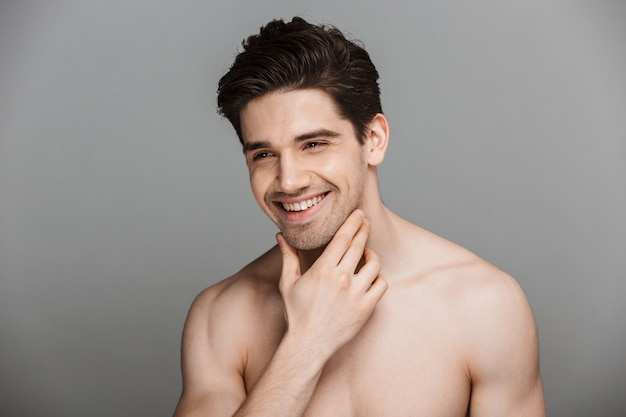 Beauty portrait of half naked laughing young man looking away