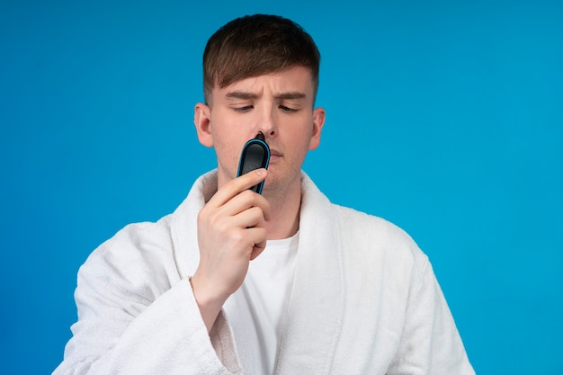 Beauty portrait of handsome guy, young man in white bath robe using electric razor or shaver to