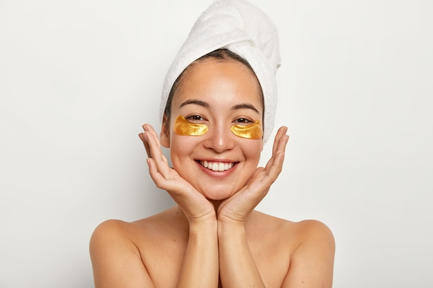 Beauty portrait of happy asian girl keeps palms near face, looks positively, shows white perfect teeth, enjoys spa procedures, stands with wrapped towel on head
