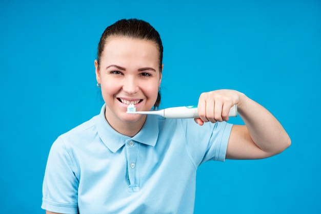 Beauty portrait of happy cheerful positive beautiful girl young woman is brushing her healthy white