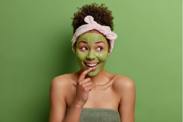Il ritratto di bellezza del modello femminile felice applica la maschera nutriente verde sul viso
