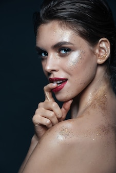 Beauty portrait of happy playful young woman with shimmering makeup over black surface
