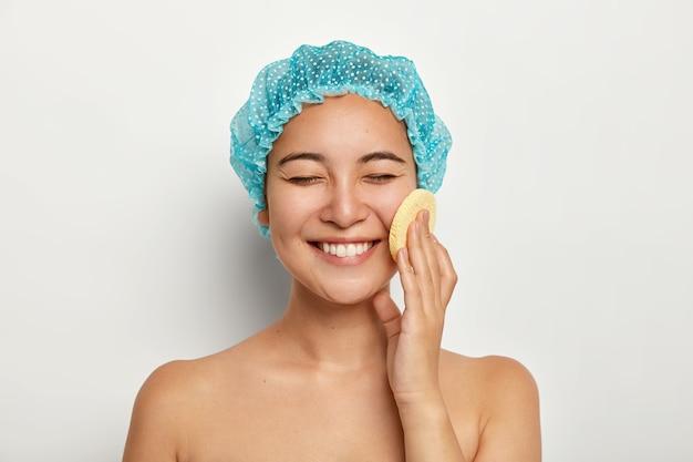 Ritratto di bellezza di felice signora sorridente dall'aspetto piacevole utilizza una spugna cosmetica per la pulizia del viso, sta nudo contro il muro bianco, vuole avere una pelle perfetta. trattamento viso, concetto di procedure termali