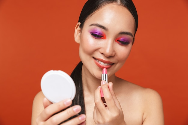 Beauty portrait of a happy young topless asian woman with brunette hair wearing bright makeup, standing isolated on red, applying lipstick while holding a mirror