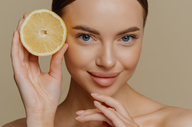 Beauty portrait of healthy young topless brunette woman touches chin gently holds half of juicy fresh lemon