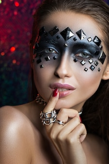 Beauty portrait of a luxurious brunette with black eyes and rhinestones