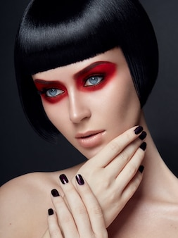 Beauty portrait of a model posing with a trendy red eyes make-up