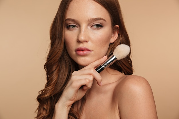 Beauty portrait of mystery ginger woman with long hair looking away while holding cosmetics brush