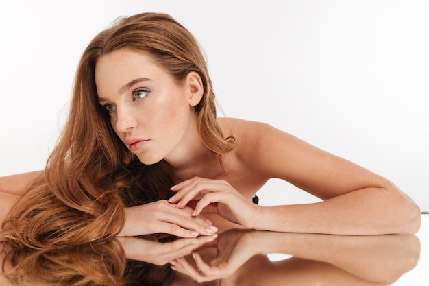 Beauty portrait of mystery ginger woman with long hair lying on mirror table while looking away