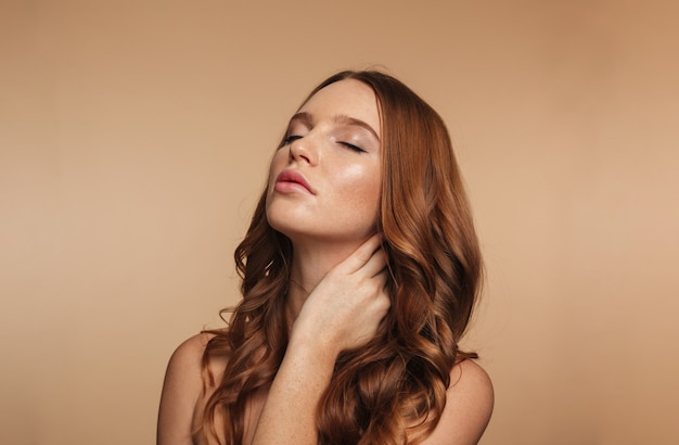 Beauty portrait of mystery ginger woman with long hair posing with closed eyes while touching her neck