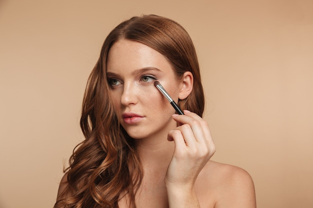Beauty portrait of mystery smiling ginger woman with long hair looking away while applying cosmetics with brush for eyeshadow