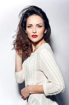 白い背景でポーズをとって波状の髪型を持つ魅力的な女性の美しさの肖像画
