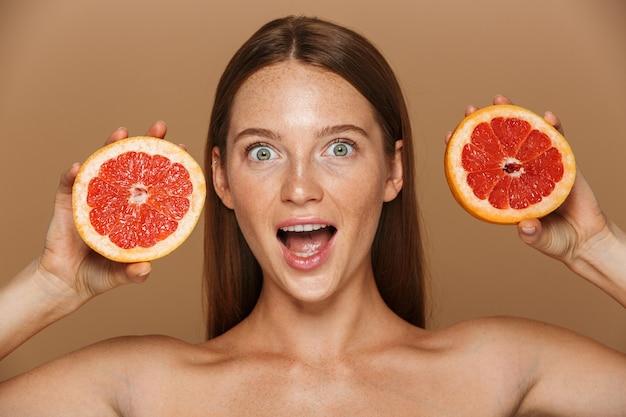 ベージュの壁に分離されたスライスされたグレープフルーツを示す長い赤い髪の美しい健康な若いトップレス女性の美しさの肖像画