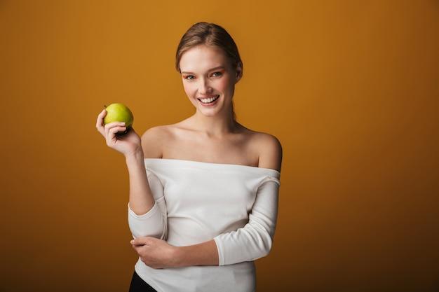 青リンゴを保持し、孤立した美しい官能的な若い女性の美しさの肖像画