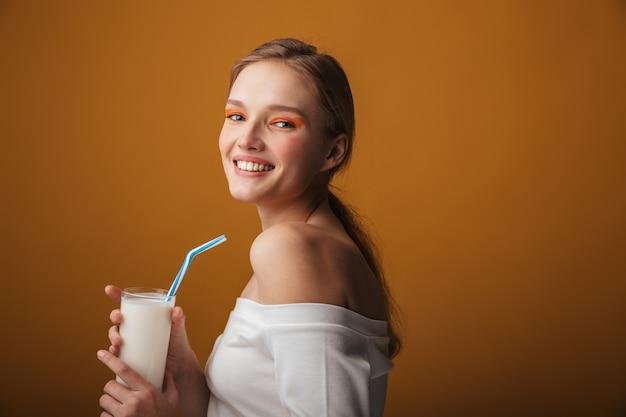 Портрет красоты молодой блондинки, носящей макияж, стоя изолированной на оранжевом фоне, держа стакан молока