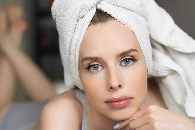 彼女の頭にタオルで陽気な魅力的な女性の美しさの肖像画