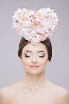 Портрет красоты девушки с креативным макияжем и цветами в форме сердца на голове