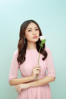 밝은 배경 위에 고립된 채 장미 꽃과 함께 포즈를 취한 사랑스러운 젊은 여성의 아름다움 초상화