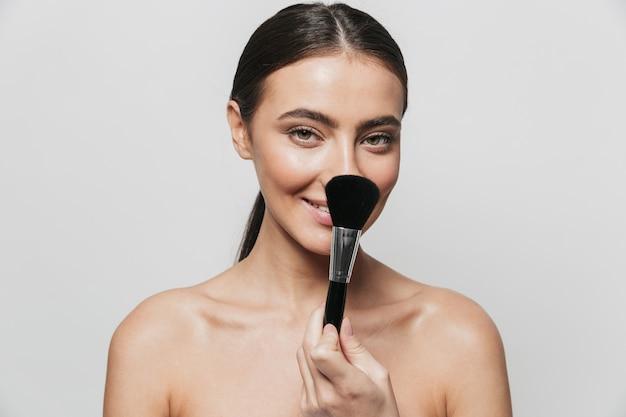 Портрет красоты довольно молодой топлес женщины, стоящей изолированно, держа кисть для макияжа