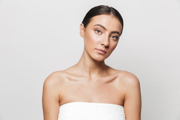 Красота портрет красивой молодой женщины, завернутой в полотенце, стоя изолированно, позирует