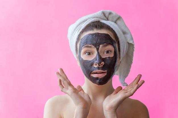 고립 된 분홍색 배경에 얼굴에 검은 영양 마스크를 적용 하는 머리에 수건에 웃는 갈색 머리 여자의 아름다움 초상화. 스킨케어 클렌징 스파 릴랙스 코스메틱 컨셉