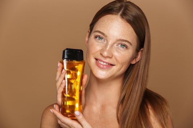 ベージュの壁に分離されたシャンプーのボトルを示す長い赤い髪の笑顔の若いトップレスの女性の美しさの肖像画