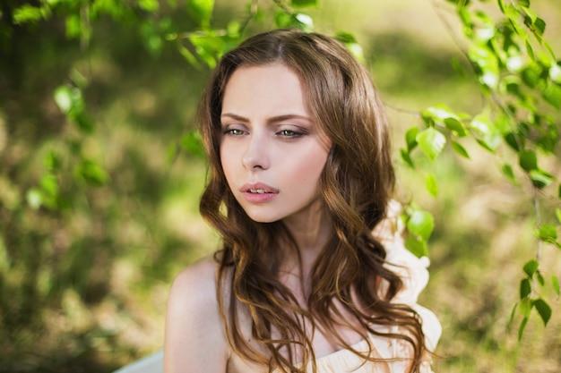非常にかなり若い女の子の美しさの肖像画。人形の外観。自然にピンクのウェディングドレスで茶色の髪の女性。長い髪。自然光。