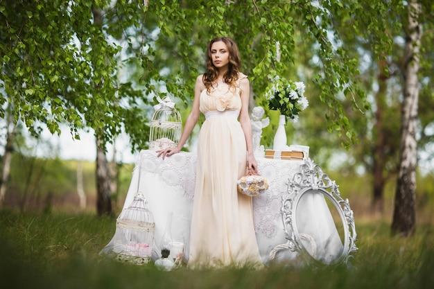 非常にきれいな若い女の子の美しさの肖像画。人形登場。結婚式の装飾に近い自然にピンクのウェディングドレスの茶色の髪を持つ女性。長い髪。自然光。自然の中でポーズをとるモデル