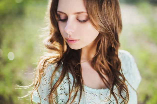 非常にかなり若い女の子の美しさの肖像画。人形の外観。自然にターコイズブルーのドレスに茶色の髪を持つ女性。長い髪。自然光。