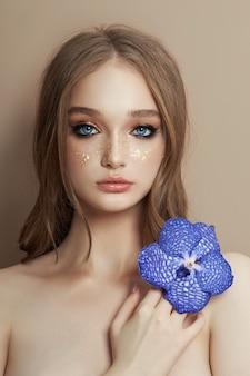 Красота портрет женщины с голубой орхидеей ванда в руке