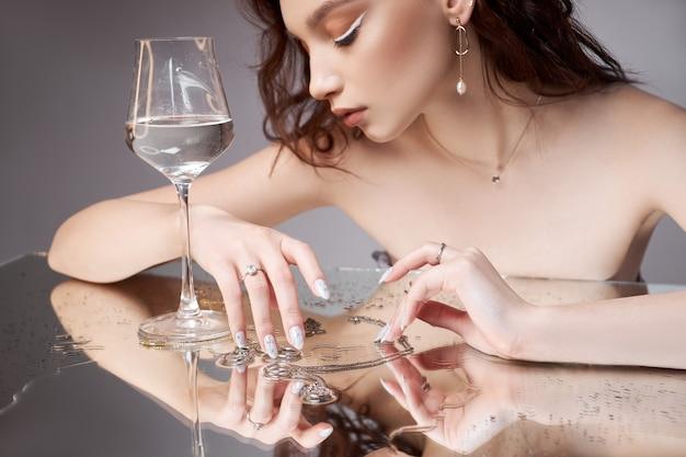 손에 유리를 가진 여자의 아름다움 초상화.