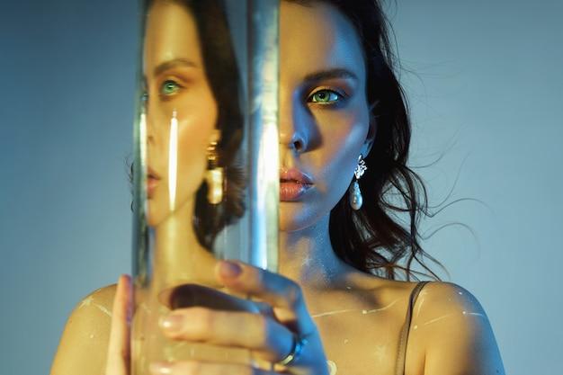 Красота портрет женщины с большим стаканом возле ее лица. искажение и преломление отражения через воду