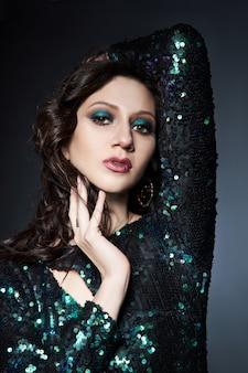 美しいイブニングメイクの女性、スパンコール付きの光沢のあるイブニングドレスのブルネットの女の子の美しさの肖像画。顔用天然化粧品