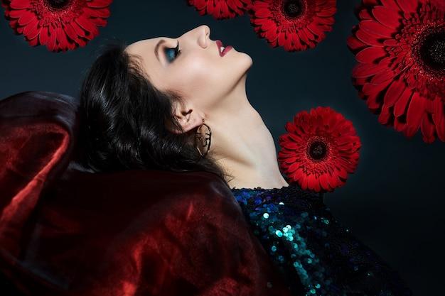 彼女の顔に美しいイブニングメイクと花を持つ女性の美しさの肖像画、スパンコールと光沢のあるイブニングドレスのブルネットの女の子。自然な顔の化粧品、花びら
