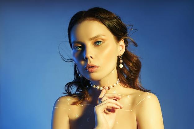 美しいメイク、イヤリング、女の子のネックレスを持つ女性の美しさの肖像画