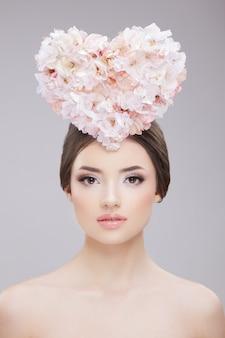 Красота портрет женщины с цветами в форме сердца на голове и обнаженным макияжем