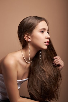 宝石、耳のイヤリング、首の周りのネックレスを持つ女性の美しさの肖像画。完璧なきれいな顔の肌、自然化粧品